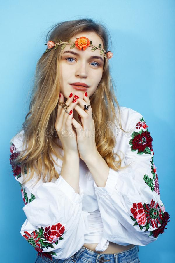 Junges hübsches blondes Mädchen, das auf blauem Hintergrund, Modearthippie boho Blumen auf Kopf aufwirft lizenzfreie stockfotos