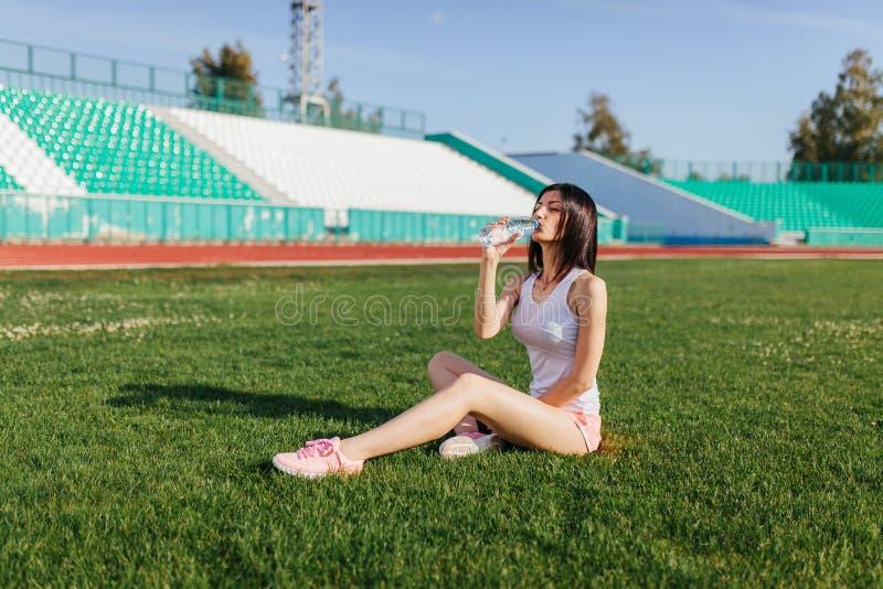 Junges hübsches brunette kaukasisches Mädchen in den rosa kurzen Hosen und Trägershirt in der Klage, die nach Sportlauf im Park a stockbild