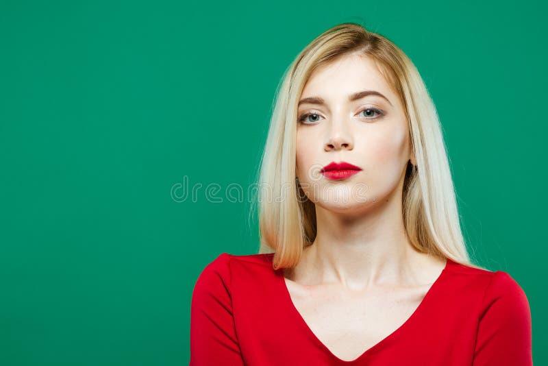 Junges hübsches Frauen-Gesicht mit den sinnlichen roten Lippen und Berufsmake-up auf grünem Hintergrund im Studio stockfotos