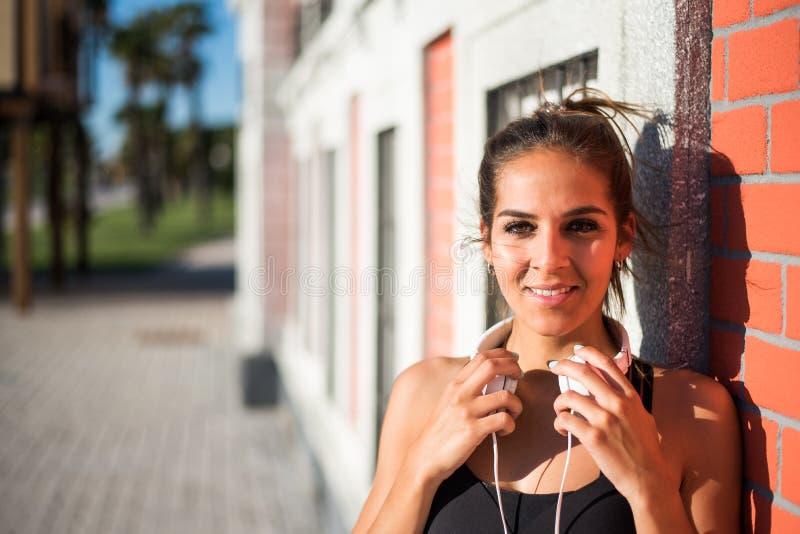 Junges hübsches Frauenlächeln lokalisiert nah herauf im Freien mit Kopfhörern stockbilder