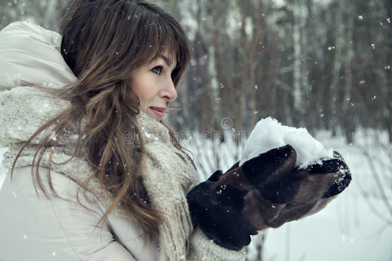 Junges hübsches Frauenporträt im Winterwald mit Schnee in den Händen stockbild