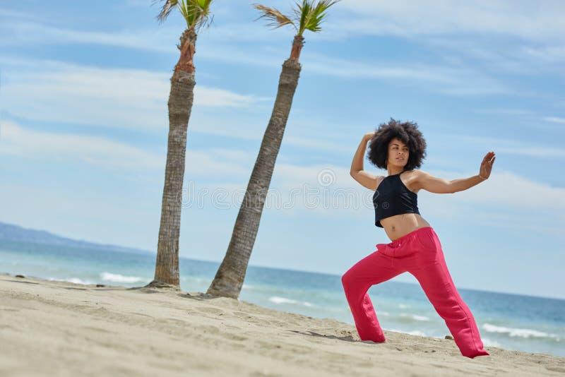 Junges hübsches Frauentrainingstanzen auf Strand stockbilder
