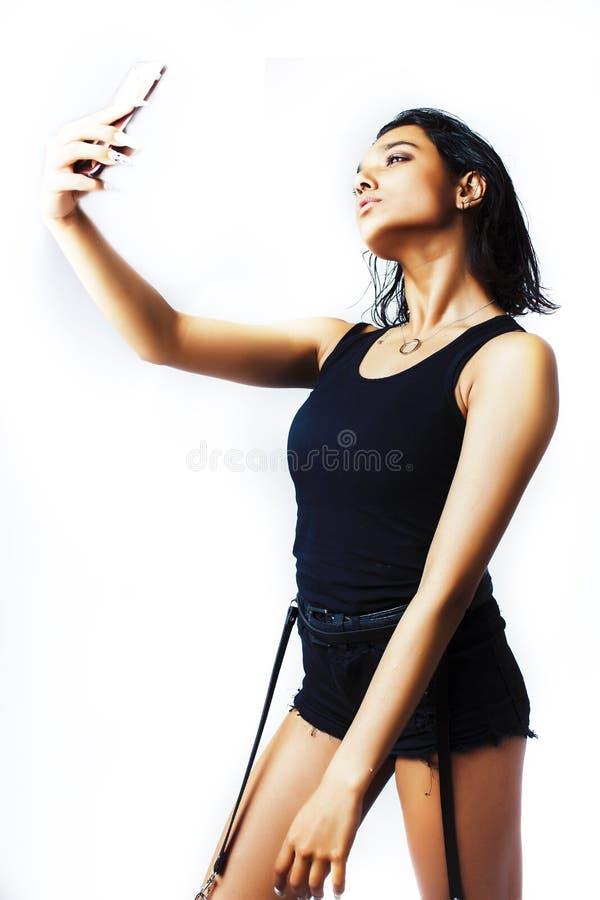 Junges hübsches indisches Mädchen, das mit dem Telefon lokalisiert auf weißem Hintergrund, Mode-Leutekonzept des Lebensstils mode stockbilder