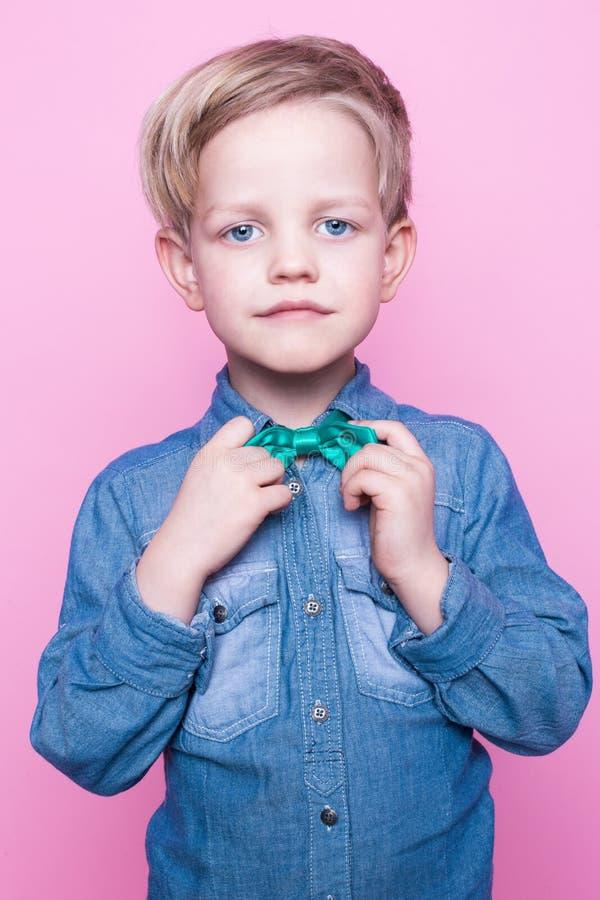 Junges hübsches Kind, das mit blauer Hemd- und Schmetterlingsbindung lächelt Studioporträt über rosa Hintergrund stockfotos