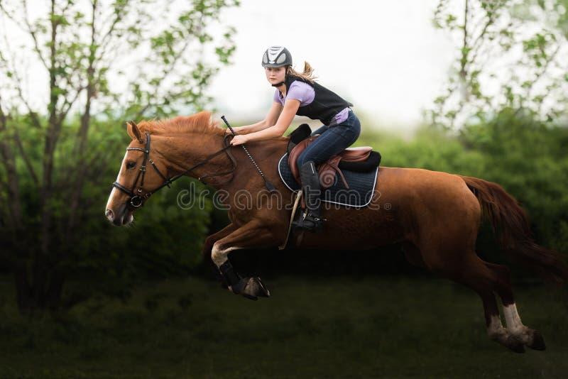 Junges hübsches Mädchen, das ein Pferd reitet lizenzfreie stockbilder