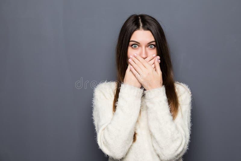 Junges hübsches Mädchen, das ihren Mund bedeckt lizenzfreies stockbild