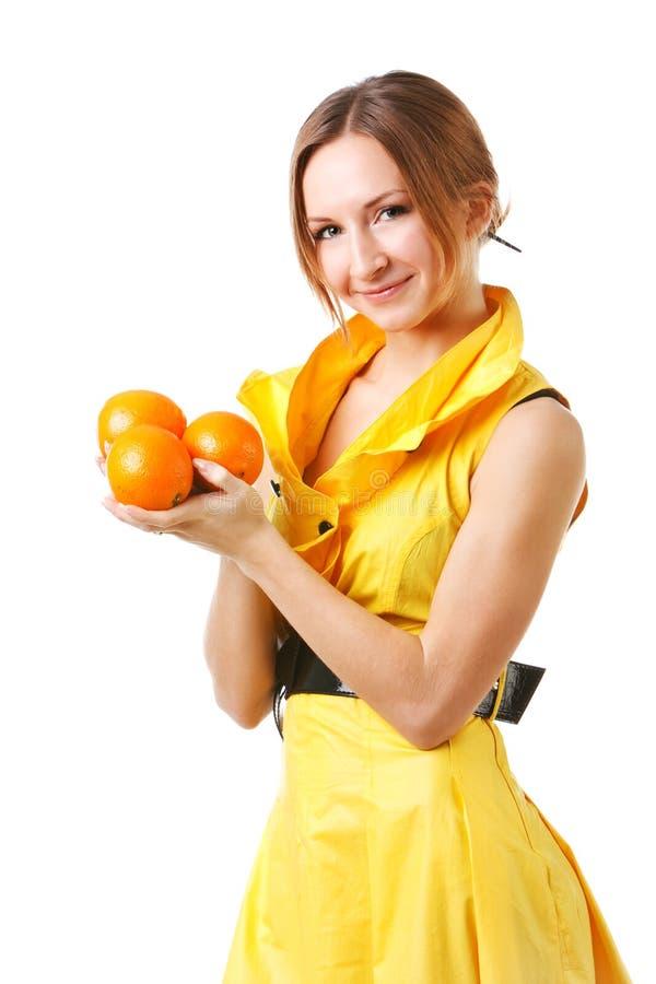 Junges hübsches Mädchen im gelben Kleid mit Orangen lizenzfreie stockbilder