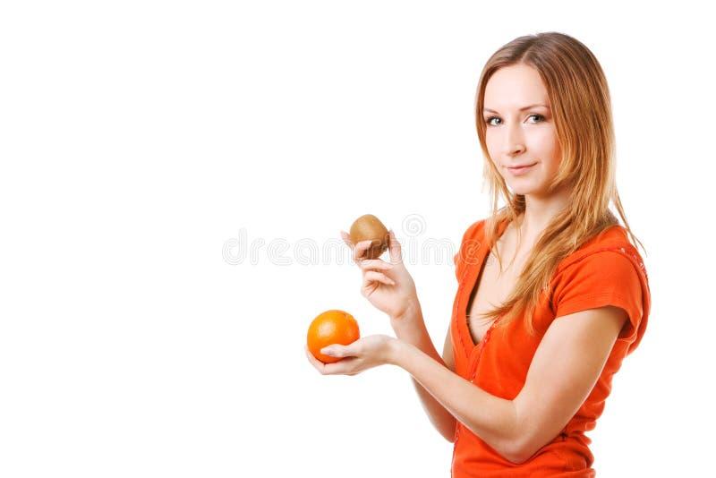 Junges hübsches Mädchen im Kleid mit Orange und Kiwi stockfoto