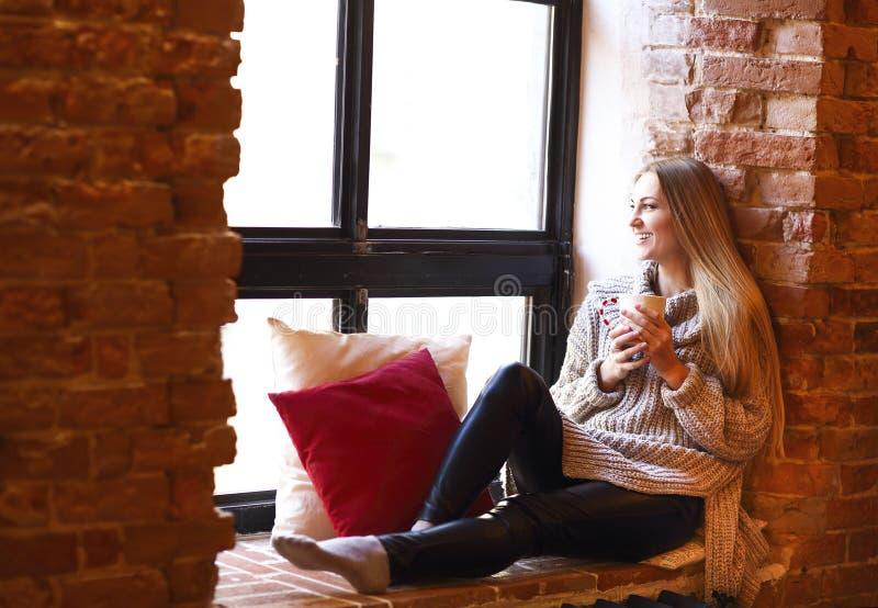 Junges hübsches Mädchen mit der Schale, die nahe Fenster sitzt stockfotografie