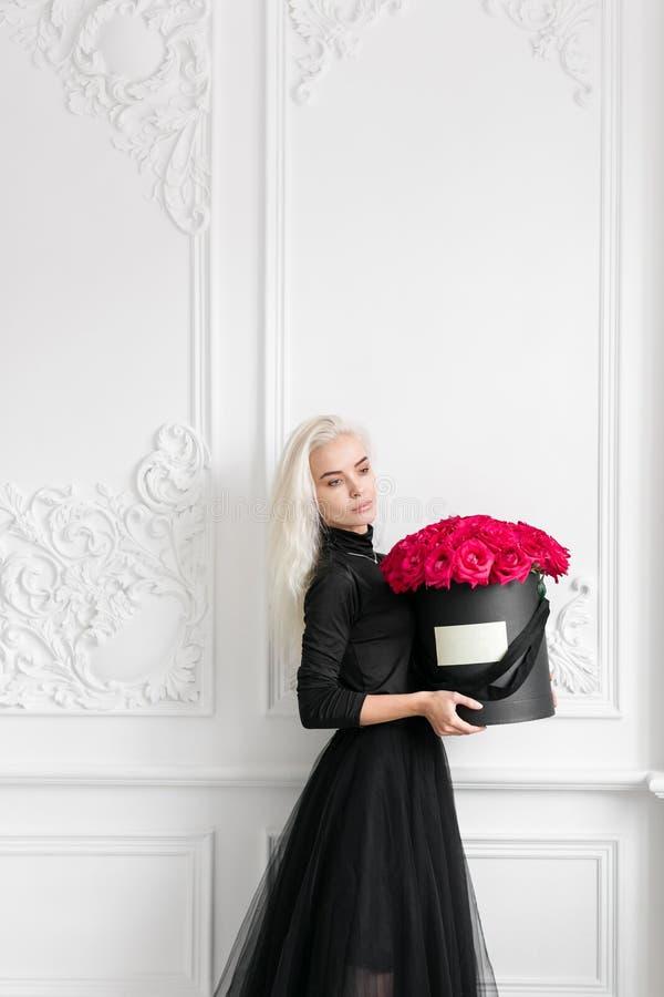Junges hübsches Mädchen mit nettem Gesicht und dem langen blonden Haar Frau, die Flugschreiber mit rosa Rosen steht und hält Art  stockbild