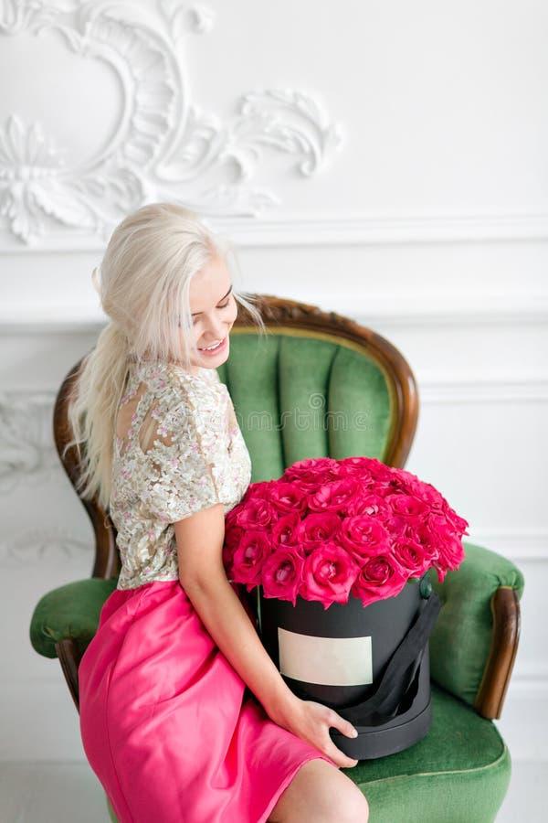 Junges hübsches Mädchen mit nettem Gesicht und dem langen blonden Haar Frau sitzt und Flugschreiber mit rosa Rosen halten Geschni stockfotos