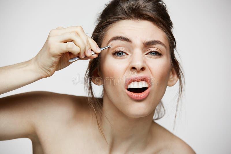 Junges hübsches Mädchen mit perfekter sauberer Haut zupfen die Augenbrauen aus, die lustiges Gesicht über weißem Hintergrund mach stockfotos