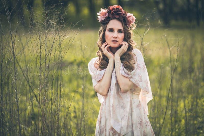 Junges hübsches Mädchen wirft mit Blumen auf lizenzfreies stockfoto