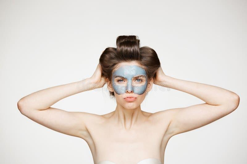 Junges hübsches nacktes Mädchen in den Haarlockenwicklern und in der Gesichtsmaske die Stirn runzelnd, Kamera über weißem Hinterg stockfoto