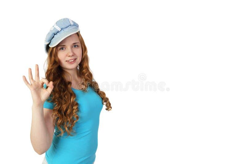 Junges hübsches Rothaarigemädchen in der Kappe zeigt okaygeste lizenzfreies stockfoto