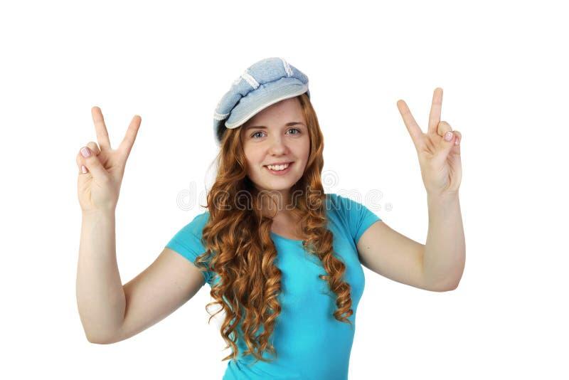 Junges hübsches Rothaarigemädchen in der Kappe zeigt Sieggeste lizenzfreie stockfotografie