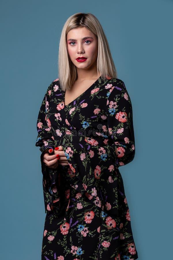 Junges hübsches sexy Mädchen mit dem blonden Haar in einem dunklen Kleid mit Blumen stockfoto