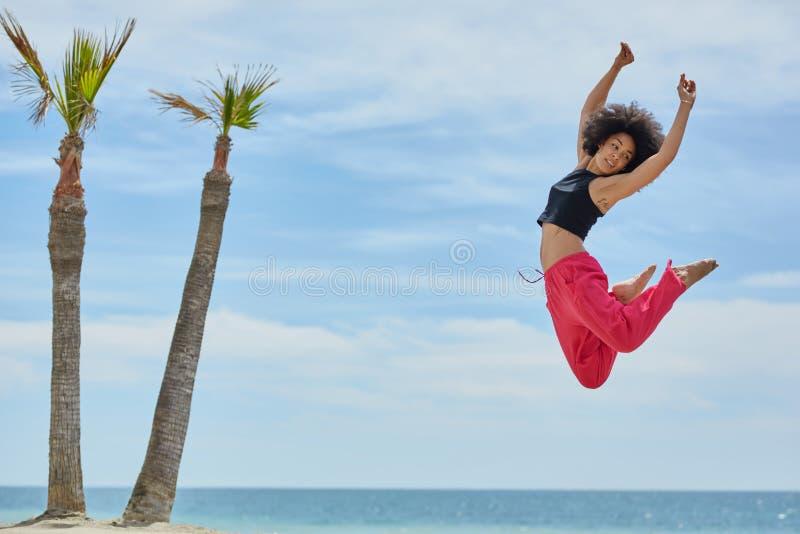 Junges hübsches Sportlerintanzen, das auf Strand springt lizenzfreie stockfotografie