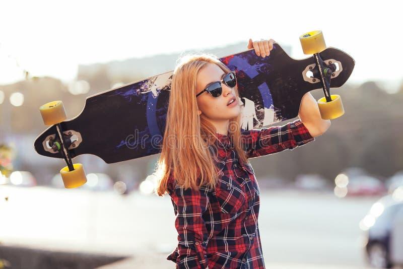 Junges Hippie-Frauenholdingskateboard hinter Kopf im Sonnenuntergang draußen Film- Art Stilvolle glückliche Hippie-Frau stockbilder