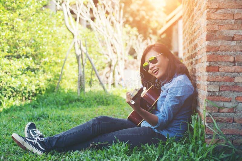 Junges Hippie-Mädchen, das eine Gitarre spielend und singend sitzt lizenzfreie stockbilder