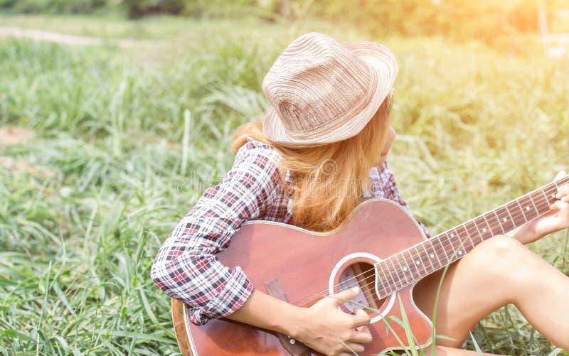Junges Hippie-M?dchen, das eine Gitarre spielend und singend sitzt stockfoto