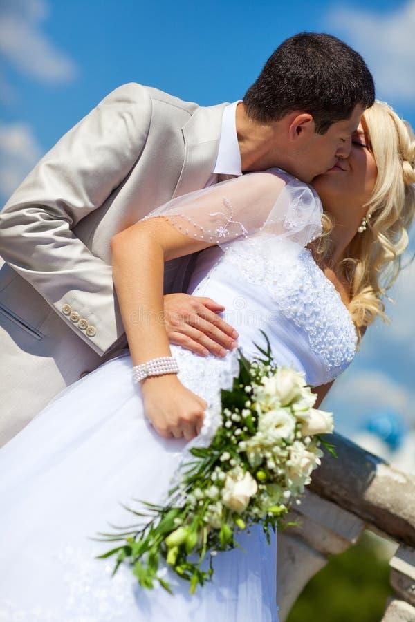 Junges Hochzeitspaarküssen lizenzfreie stockfotografie