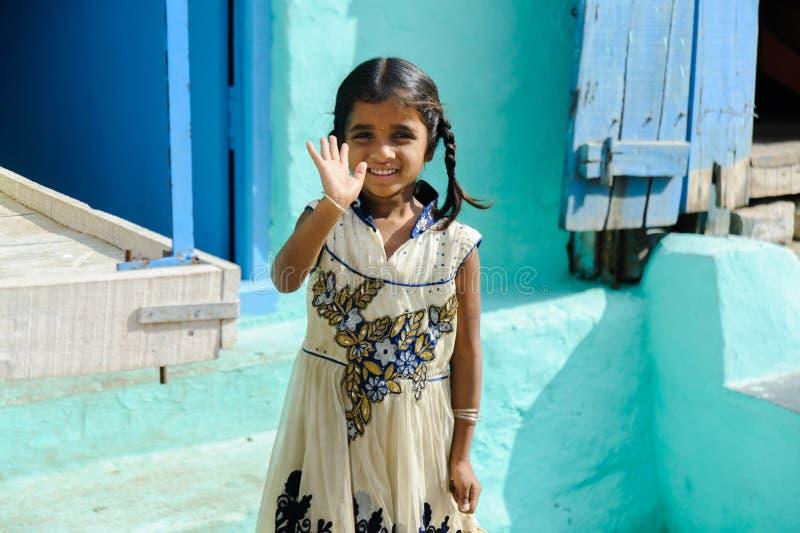 Junges indisches Mädchen, das eigenhändig in Freien am 11. Februar 2018 Puttaparthi, Indien lächelt und in camera wellenartig bew stockfotos