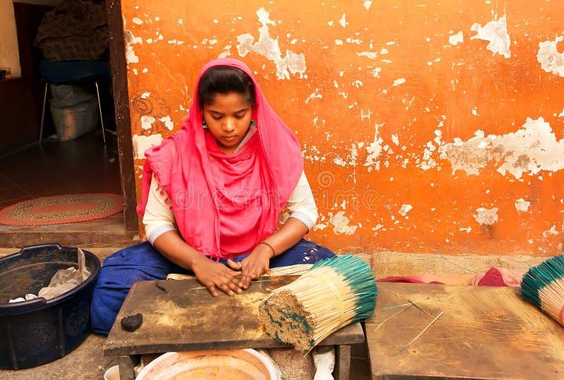 Junges indisches Mädchen, das mit Aromasandelholzweihrauch am traditionellen Haus mit bunten Wänden arbeitet stockfoto