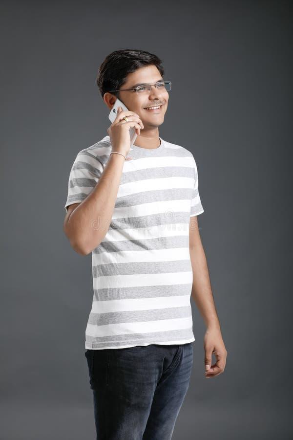 Junges indisches Mannholdingmobile in der Hand lizenzfreie stockfotos