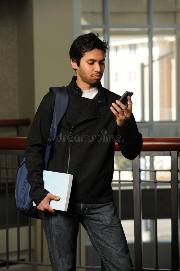 Junges indisches Srudent unter Verwendung des Mobiltelefons lizenzfreies stockfoto