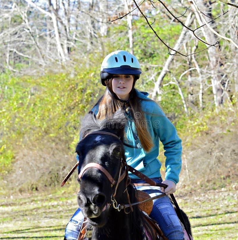 Junges jugendlich-Mädchen, das ein Pferd reitet lizenzfreie stockfotografie