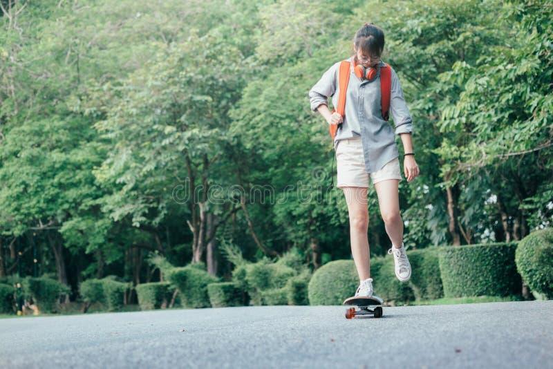 Junges jugendlich Mädchenreiten asean auf longboard auf der Straße lizenzfreies stockfoto