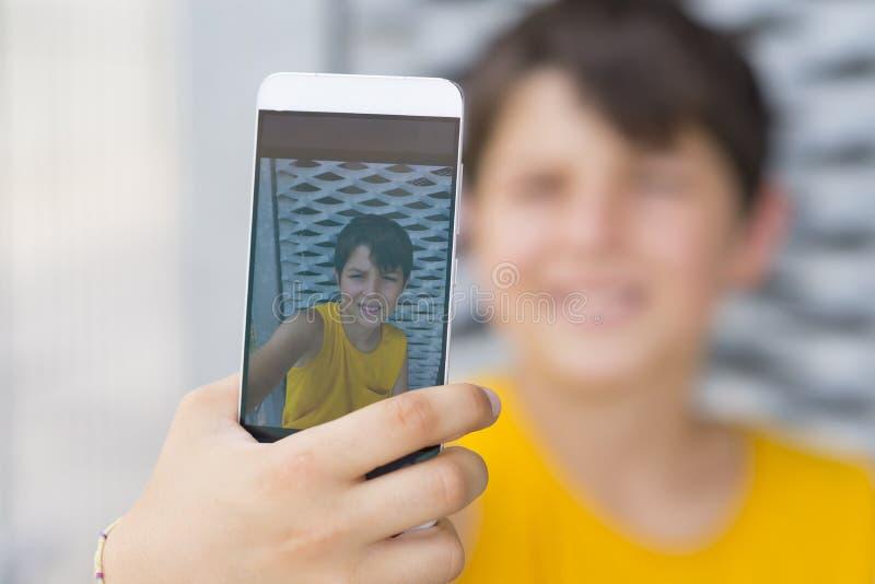 Junges jugendlich unter Verwendung seines Telefons draußen und ein selfie machend lizenzfreies stockfoto