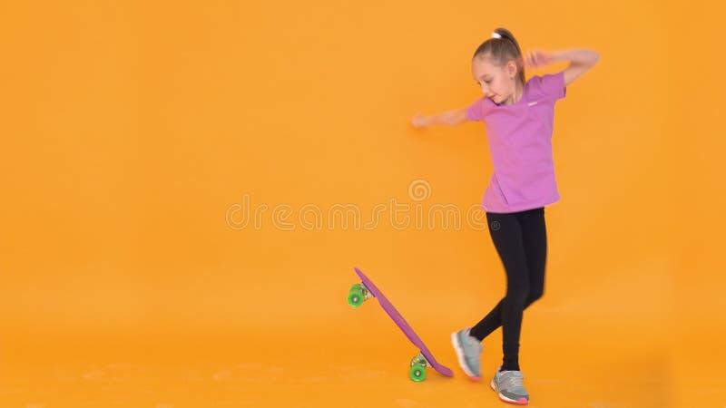 Junges Jugendlichmädchen, das auf Skateboard im Studio auf orange Hintergrund balanciert stockfoto