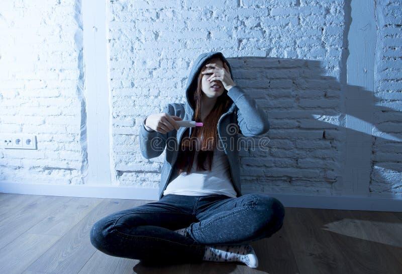 Junges Jugendlichmädchen oder junge Frau im Schock erschraken nach positivem Schwangerschaftstest lizenzfreie stockfotografie