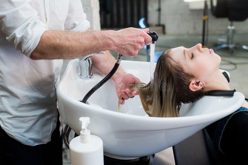 Junges Jugendlichmädchen in waschendem Haar des Frisörsalons durch die Hände des männlichen Friseurs stockfotos