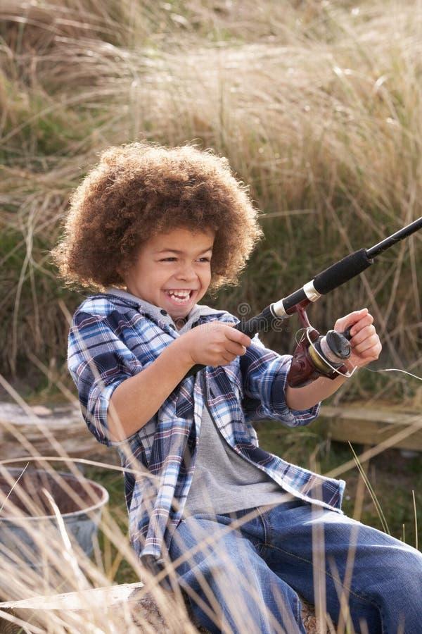 Junges Jungen-Fischen an der Küste lizenzfreies stockfoto