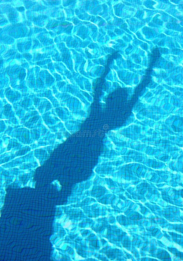 Junges Jungenschattentauchen im Swimmingpool stockfotografie