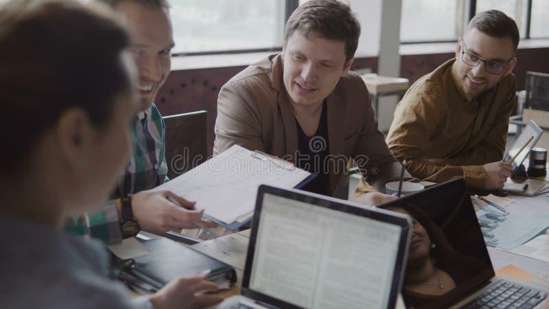 Junges Jungunternehmen im modischen Büro Die multiethnische Gruppe von Personen, die Finanzdaten bespricht, benutzen Dokument und stockbild