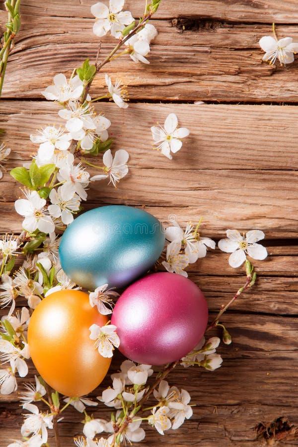 Junges Küken in Wanne, 2 malte Eier und Blumen lizenzfreie stockfotografie
