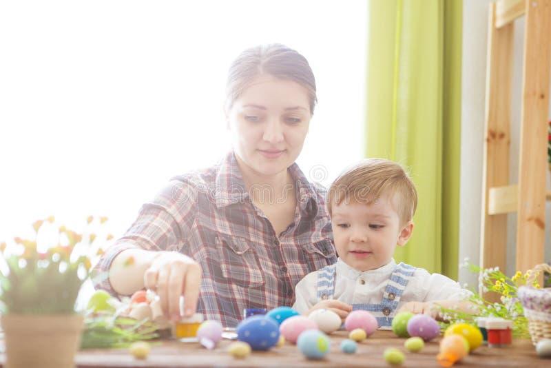 Junges Küken in Wanne, 2 malte Eier und Blumen Glückliche Mutter und ihr nettes Kind, die zu Ostern durch das Malen der Eier fert stockfoto
