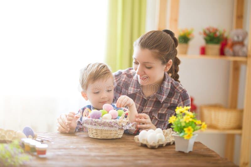 Junges Küken in Wanne, 2 malte Eier und Blumen Glückliche Mutter und ihr nettes Kind, die zu Ostern durch das Malen der Eier fert stockfotografie