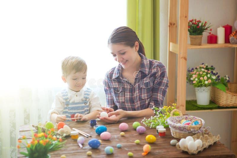 Junges Küken in Wanne, 2 malte Eier und Blumen Glückliche Mutter und ihr nettes Kind, die zu Ostern durch das Malen der Eier fert lizenzfreie stockfotos