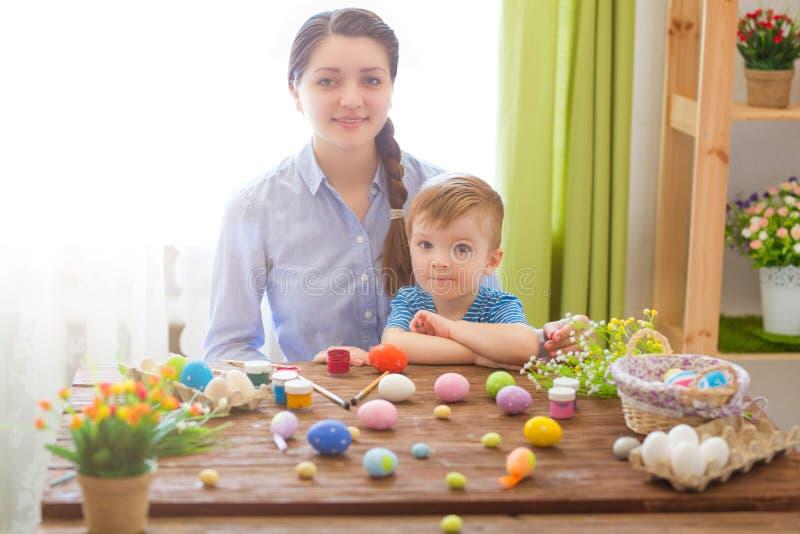 Junges Küken in Wanne, 2 malte Eier und Blumen Glückliche Mutter und ihr nettes Kind, die zu Ostern durch das Malen der Eier fert stockbilder