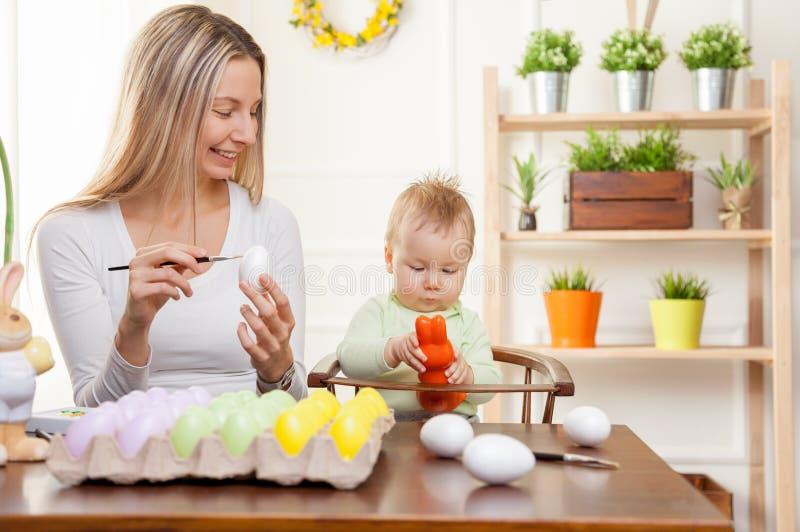 Junges Küken in Wanne, 2 malte Eier und Blumen Glückliche Mutter und ihr nettes Kind, die zu Ostern fertig wird lizenzfreies stockbild