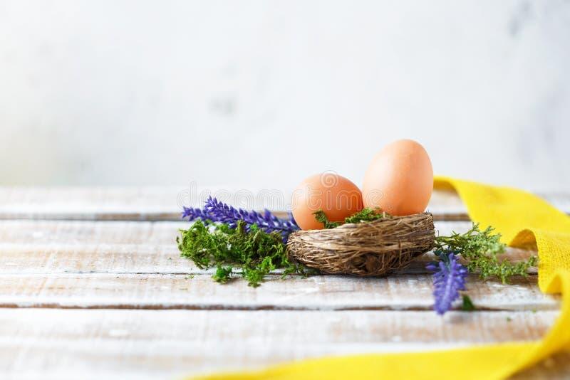 Junges Küken in Wanne, 2 malte Eier und Blumen Helle Frühlingsblumen mit Ostereiern nahe einer gelben dekorativen Laterne stockfotos