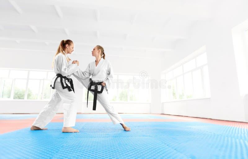 Junges Karatemädchen, das zu ihrem Partner ausdehnt Bein vor der Ausbildung hilft lizenzfreie stockfotografie