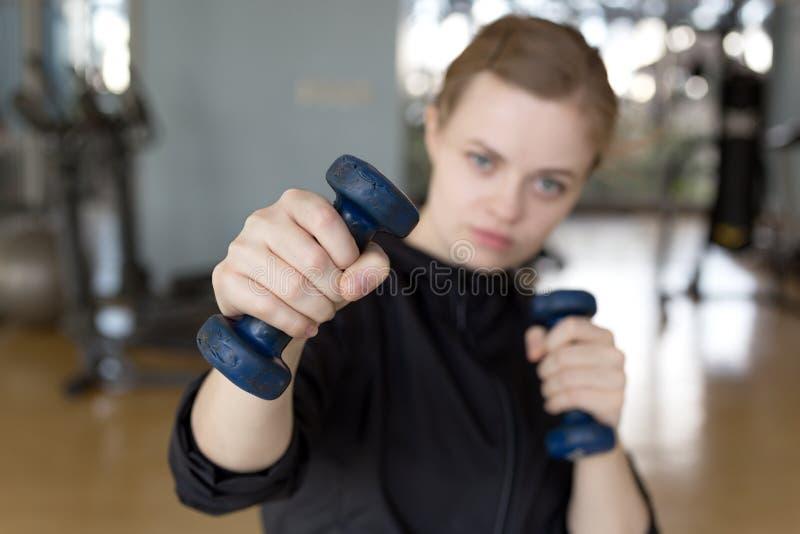 Junges kaukasisches Frauenmädchen, das Training mit hellen Dummköpfen an der Turnhalle, anhebende Gewichte tut lizenzfreies stockfoto