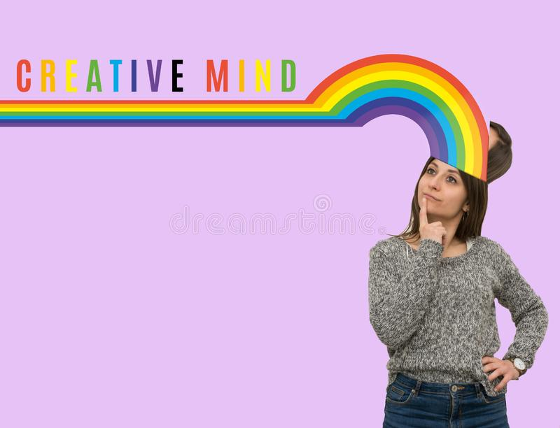 Junges kaukasisches Mädchen mit dem Regenbogen, der aus ihren Kopf herauskommt Hand, die lego Wand aufbaut lizenzfreie stockfotos
