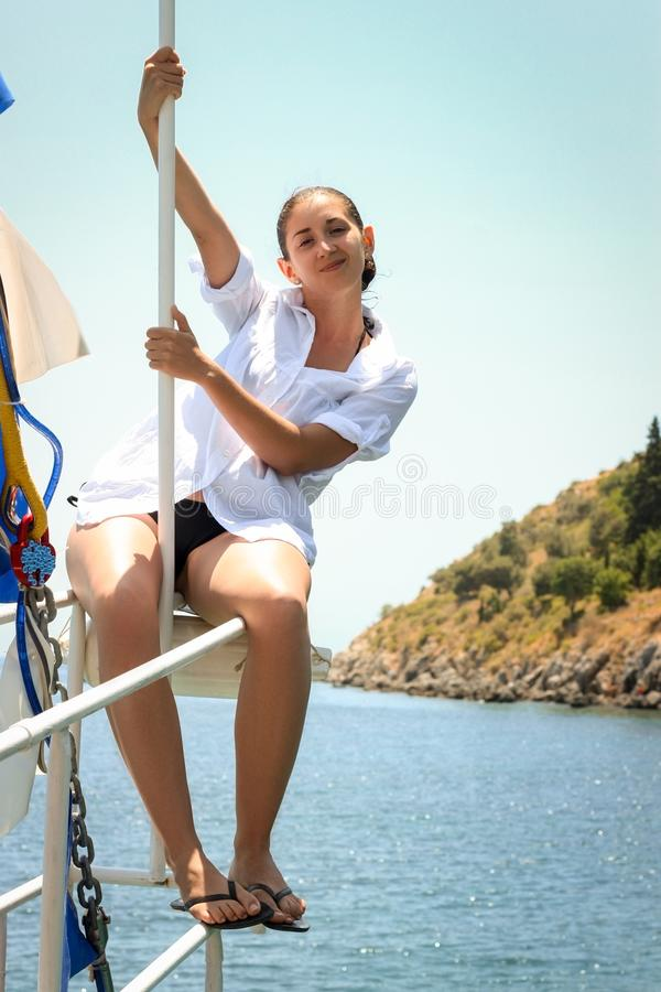 Junges kaukasisches weibliches Modell, das auf dem Bogen der Yacht halten durch Pfosten aufwirft Im Hintergrundmeer und -hügel lizenzfreies stockbild